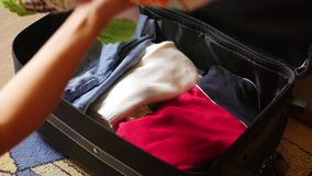 Woman puts things in a suitcase stock video footage
