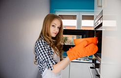 Woman puts to the microwave bowl with meal Royalty Free Stock Photography