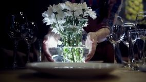 Woman puts vase of flowers on table. Action. Close-up of woman puts vase of white flowers on serving table with