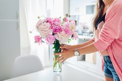 Woman puts vase with peonies. Housewife taking care of coziness in kitchen. Modern kitchen design stock image