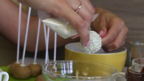 A woman puts a white icing on the cake pops, covered with white chocolate. For even distribution of the dressing on the ball. A woman puts a white icing on the stock video footage