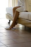 Woman puts white slippers on Royalty Free Stock Images