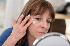 Woman putting anti-age cream on her face. Mature woman putting anti-age cream on her face stock photography