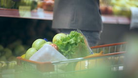 Woman putting apples in trolley at grocery section of supermarket.  stock video footage