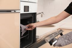 Woman putting baking tray into electric oven in kitchen stock photos