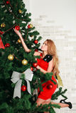 Woman putting a balls on christmas tree Royalty Free Stock Image