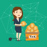 Woman putting bitcoin coin in box for taxes. Chained to a ball upset taxpayer standing near the box full of golden bitcoin coins for the payment of taxes Royalty Free Stock Photo