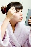 Woman putting black mascara. Young beautiful woman looking in the mirror and putting mascara stock photos