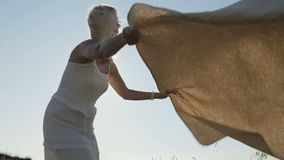 Woman putting a blanket on the ground on nature at sunset. Slow motion