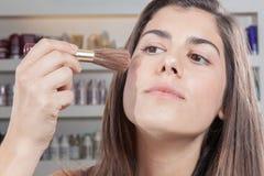 Woman putting blush on her cheeks Stock Photo