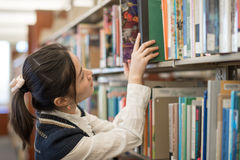Woman putting book back onto a bookshelf Royalty Free Stock Images