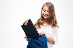 Woman putting book into backpack Stock Images