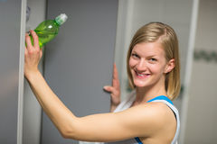 Woman putting bottle in locker at healthclub Stock Images