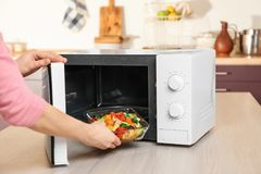 Woman putting bowl with vegetables in microwave oven. Closeup Stock Image