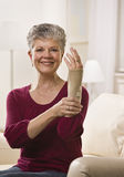 Woman Putting Brace on Hand. An elderly woman is putting a brace onto her hand and smiling at the camera.  Vertically framed shot Stock Photography