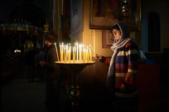 A woman is putting a candle and praying. A woman is putting a candle and praying before candela in The Holy Trinity Cathedral of the Russian Orthodox Church in Royalty Free Stock Photo