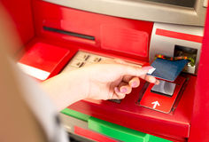 Woman putting card in ATM cash machine Stock Image