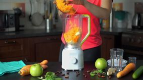 Woman Putting Carrots and Apples into a Blender. Woman Putting Grated Carrots and Chopped Apples into a Blender to Prepare Healthy Detox Green Smoothie. Healthy stock video
