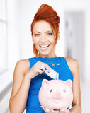 Woman putting cash money into piggy bank Royalty Free Stock Photos