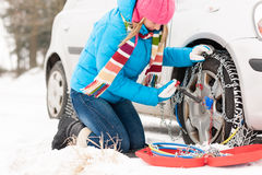 Woman putting chains on car winter tires. Woman putting chains on car tires snow broken winter fixing Royalty Free Stock Photos