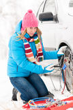 Woman putting chains on car winter tires. Woman putting chains on car tires snow broken winter fixing Royalty Free Stock Images