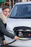 Woman charging an electric car stock photography