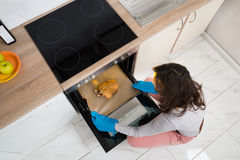 Woman Putting Chicken In Oven Stock Photos
