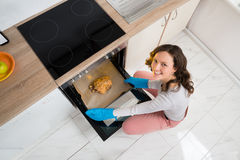 Woman Putting Chicken In Oven Royalty Free Stock Photography