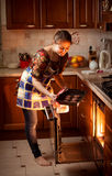 Woman putting chocolate cookies in hot oven Royalty Free Stock Photo