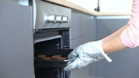 Woman putting chocolate cookies in oven, recipes of homemade baking, confection. Stock footage stock video