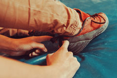 Woman putting on climbing shoes Royalty Free Stock Photography