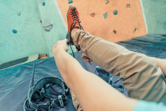 Woman putting on climbing shoes Stock Images