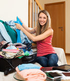 Woman putting clothes and accessories into suitcase Stock Photography