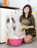 Woman putting clothes in to washing machine Stock Photo