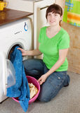 Woman putting clothes into washing machine Stock Photos