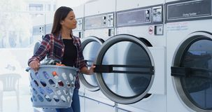 Woman putting clothes into washing machine 4k. Woman putting clothes into washing machine at laundromat 4k stock footage