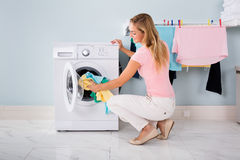 Woman Putting Clothes In Washing Machine. Woman Loading Dirty Clothes In Washing Machine For Washing In Utility Room royalty free stock images