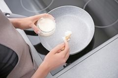 Woman putting coconut oil on frying pan in kitchen,. Closeup stock photo