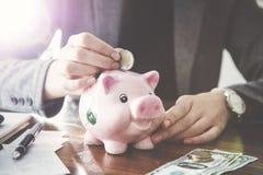 Woman putting coin money to pink piggy money box. Woman putting coin money  to pink piggy money box Stock Photos