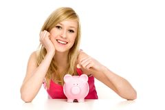 Woman putting coin in piggy bank Stock Images