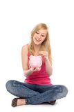 Woman putting coin in piggy bank Royalty Free Stock Photography