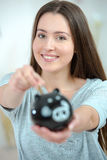 Woman putting coin into piggy bank Royalty Free Stock Images
