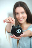 Woman putting coin into piggy bank Royalty Free Stock Photo