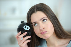 Woman putting coin into piggy bank Stock Photo
