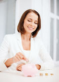 Woman putting coin into piggy bank Royalty Free Stock Photography
