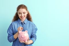 Woman putting coin into piggy bank on color background. Money savings concept stock photo