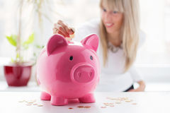 Woman putting coin in piggy bank Stock Photos