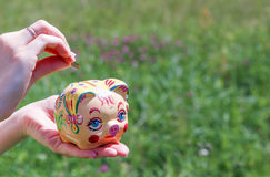 Woman Putting Coin In Piggy Bank. Woman Putting Coin In Piggy Bank handmade, outdoors Royalty Free Stock Photos