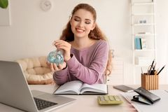 Woman putting coin into piggy bank indoors. Money savings concept stock image