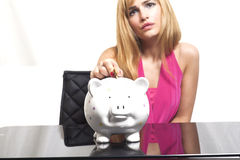 Woman putting coin in piggy bank Stock Photography